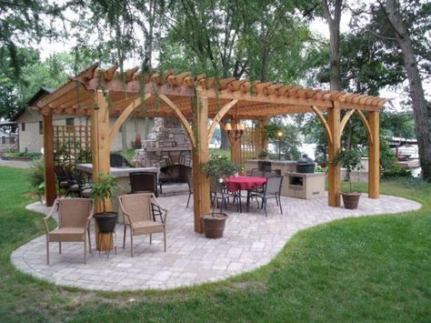 Lakeside Outdoor Kitchen, Built on a 700 sq. ft. patio, this Outdoor Living Space was made to entertain. Two bar and grill islands fully equipped with a refrigerator, gas grill, deep fryers, Big Green Egg Smoker and more make this space a fully-functional kitchen. A wood-burning stone fireplace with built-in wood storage is the centerpiece of the room, providing the heat and atmosphere to extend the party into the evening. The solid-cedar pergola not only helps to define the space, but also…