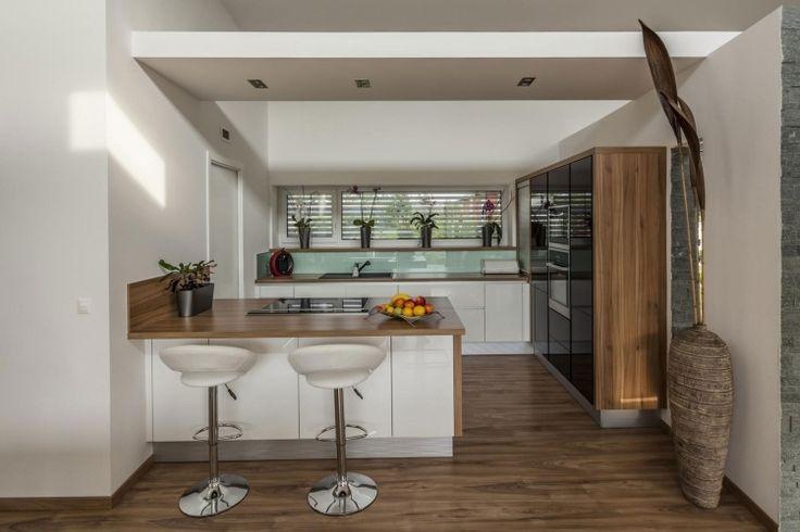 große Küche mit Kochinsel in weiß und holz - mintgrüner Spritzschutz