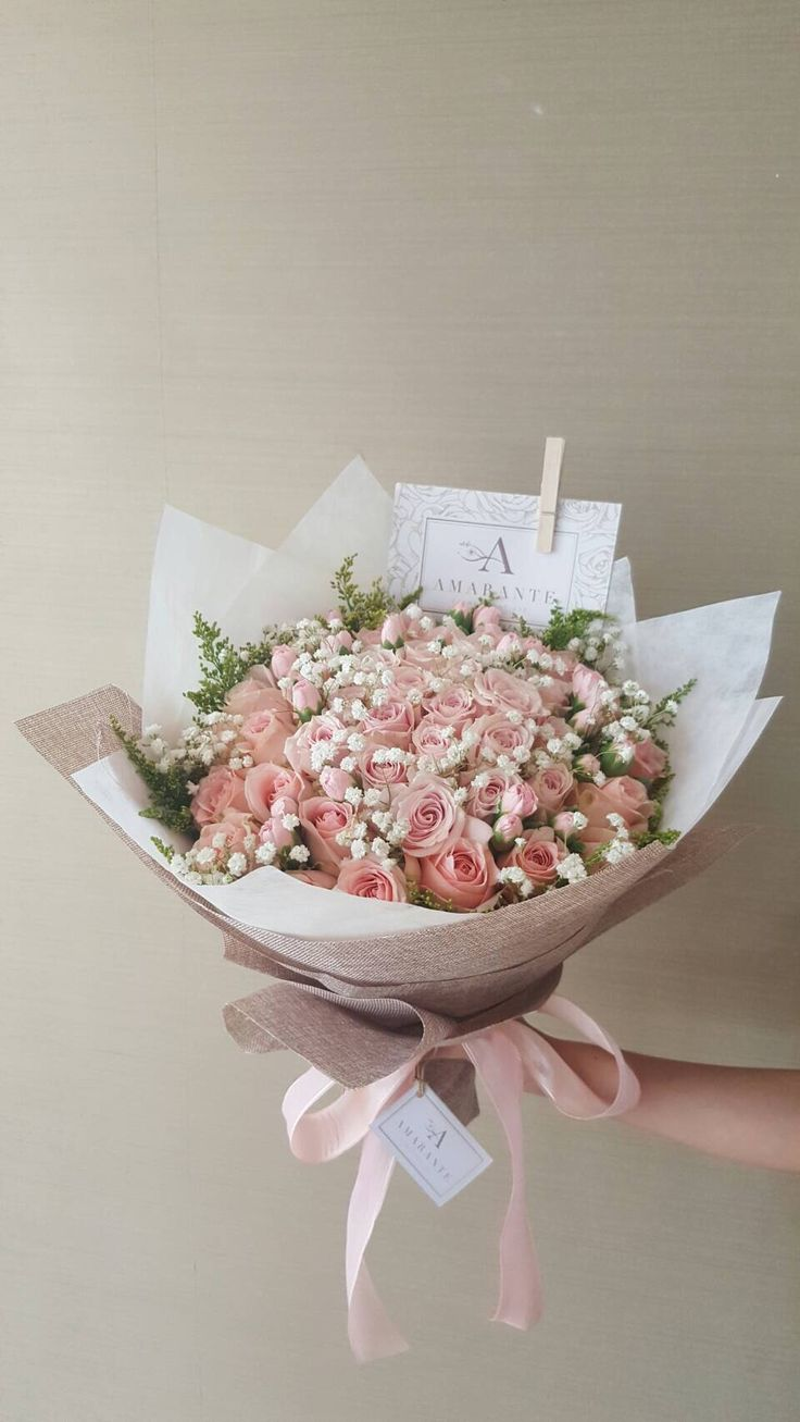 Pink Avalanche Roses with Baby Breath wrapped in natural jute paper.