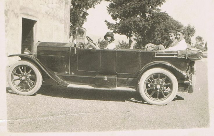 With a car, in front of the Villa.