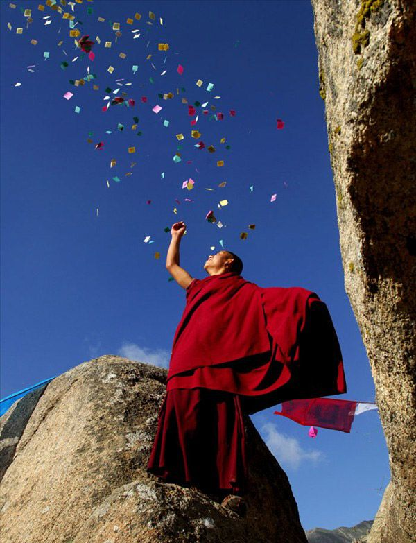 """A monk in crimson robe scatters the colorful sutra streamers, which symbol auspiciousness, into the sky. The photo taken by Fan Linsuo from Hebei Province is an entry in the first """"Impressions on Tibet"""" Photography Contest co-organized by China Tibet Online and China Photographers Association. (Photo/China Tibet Online)"""