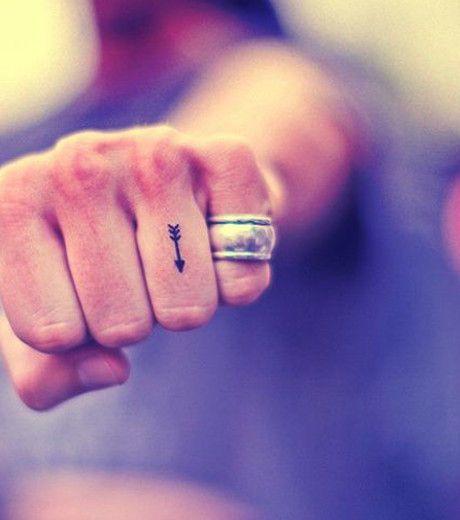 Photo : Tatouage: deux flèches croisées sur le bras, indiquent les différents pôles