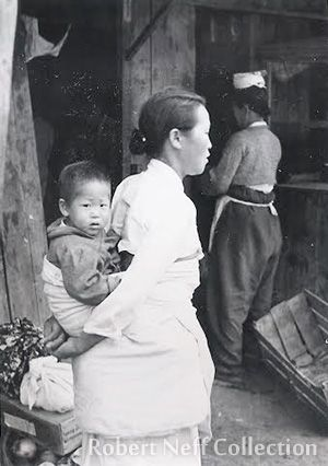 Life in Chuncheon during the Korean War. Photo by Fred Dustin. A mother carries her young child.