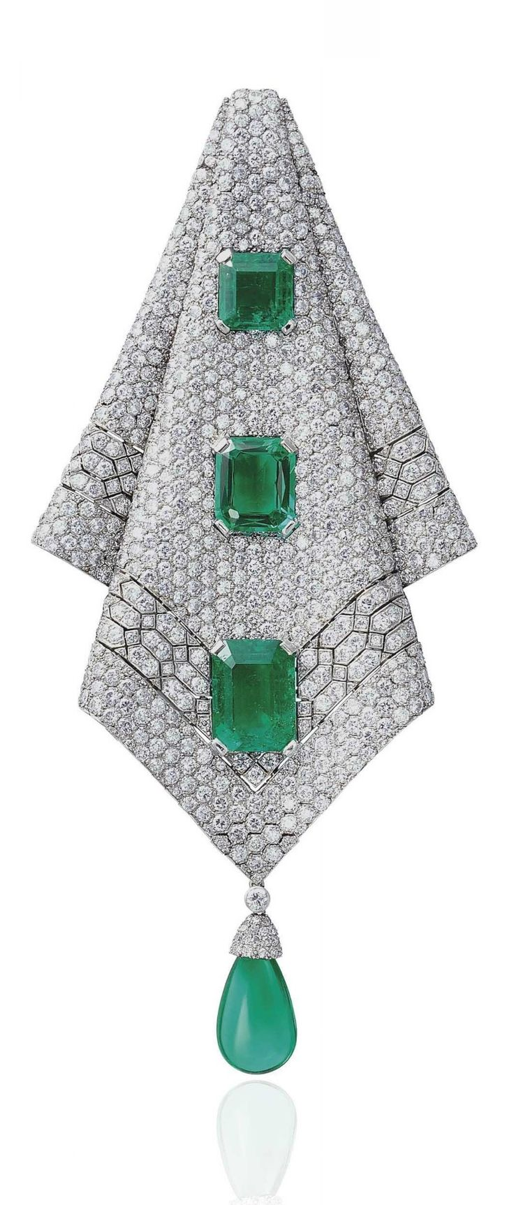 AN EXQUISITE ART DECO EMERALD AND DIAMOND PENDANT, LATE 1930S. Modelled as a diamond-set articulated folded cloth, set with three octagonal step-cut emeralds, weighing approximately 10.87, 6.29 and 4.73 carats, to the drop-shaped emerald pendant, late 1930s, 14.0 cm.