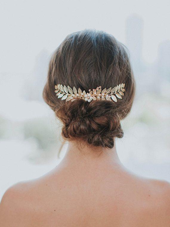Casco Ariadnê  Hojas de un peine del pelo de la hoja de oro con oro, brillantes cristales de Swarovski y brotes perlados opalescentes encadenados a lo largo de una rama. Este casco de la boda se acaba con un peine de oro. La pieza de cabello funciona muy bien como accesorio de boda inspirado Grecian. La peluca de la hoja de laurel funciona muy bien con el pelo hacia abajo o hacia arriba.  En la foto en oro. La foto final muestra la plata en el pelo Ariadnê.  Peine del pelo de Ariadnê…