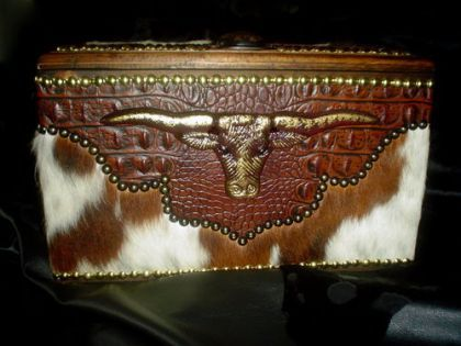 """Here is a beautiful and useful small decorative trunk, shown covered in soft Tri-Colored hair on hide and embossed brown Aligator leather.It is accented with French Natural and Renaissance hand placed Tacking and a """"Hand Painted"""" cast iron longhorn on the front.There are Mission style handles on each side, that are both decoratice and useful, Read more..."""