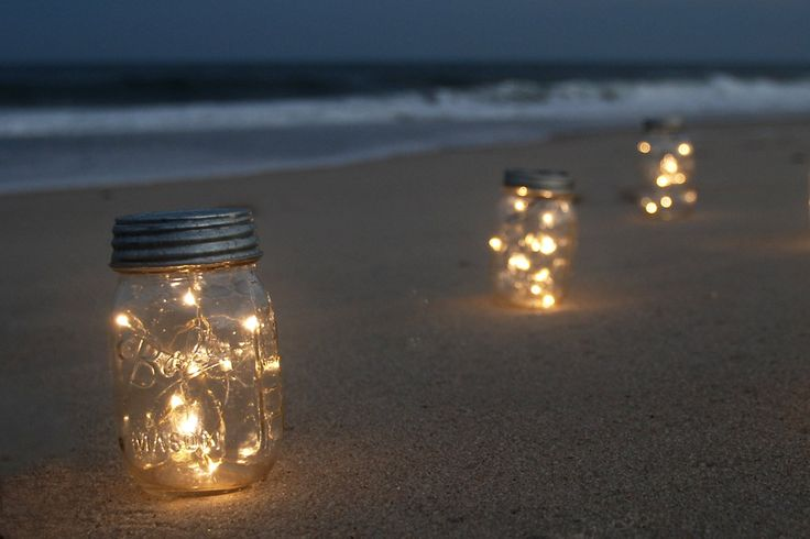 15 Garden Lanterns that Will Transform Your Yard to Romance Novel Status | How Does She  Although these are on the beach, I think they'd make beautiful garden lights.  Simple sitting mason jars and firefly lights.
