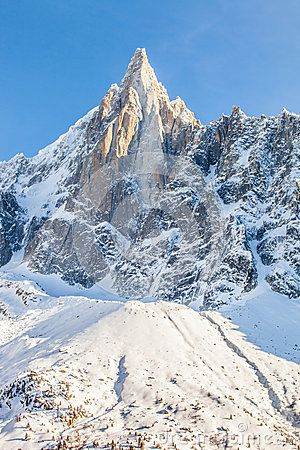 Close up view of Les Drus peak in the Mont Blanc massif in the French Alps with ski slopes at its base