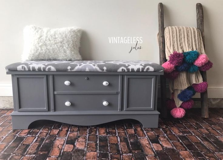 """""""...This vintage Lane cedar chest has been painted in General Finishes Driftwood Milk Paint and sealed with High Performance Topcoat. Seat pad re-upholstered with a designer fabric in shades of gray and white. The same fabric was used to line the interior tray. Distressed white ceramic knobs were added to make a statement against the medium gray tone."""" - Vintageless Jules"""
