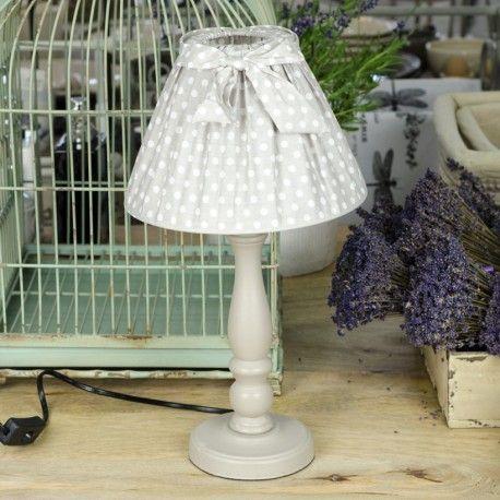 Śliczna stojąca lampa w stylu prowansalskim, z szarą podstawą oraz z abażurem ozdobionym w białe kropeczki i uroczą kokardką.