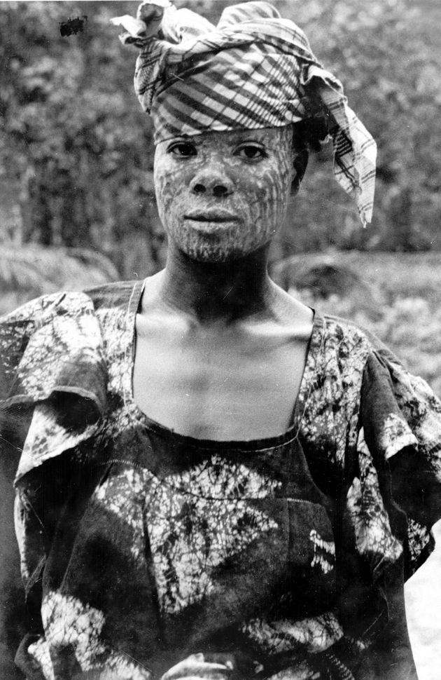 Africa    Portrait of Liberian woman in batik dress with plaid headscarf. She wears chalk on her face, which is worn for Sande Society initiation ceremonies and as a traditional cure. Liberia, Margibi, Harbel.   ©Eugene Manis, ca. 1939 - 1941