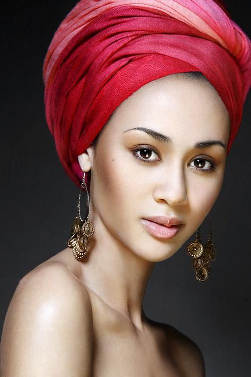 African head wraps can transform a look when used judiciously. The turban style  monochromatic color and soft  fabric accentuates her face shape.The  loop  earings completes the whole look. A clever use of the turban style head wrap.