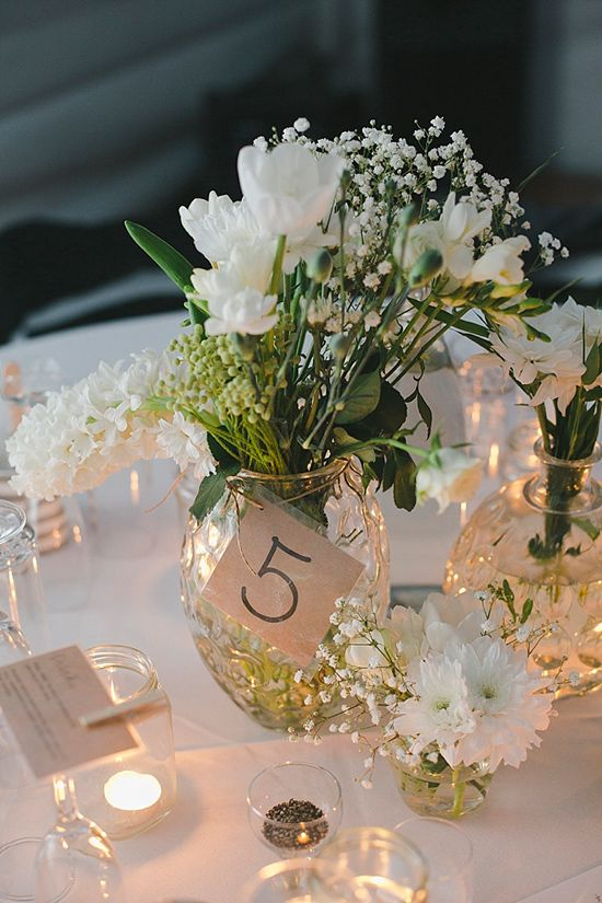 Cute idea for setting little floating candles in small holders around the mason jars with flowers centerpieces