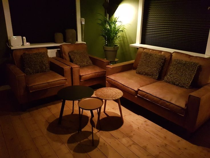 Mooie nieuwe woonkamer cognackleurige bank en stoelen en mooie groene muur