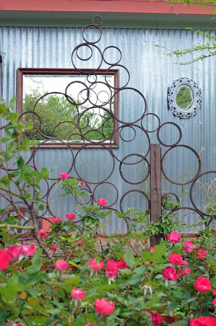 Eddie created these steel ring trellises in the side garden. Mirrors hang like windows on the exterior walls of the house, creating a greate...
