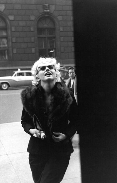 A rare candid shot of Marilyn, out and about in NYC in 1955, wearing sunglasses and a fur-trimmed black suit with a clutch bag under her arm.