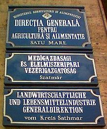 Agglutination - The middle sign is in Hungarian, which agglutinates extensively. (The top and bottom signs are in Romanian and German, respectively, both inflecting languages.)