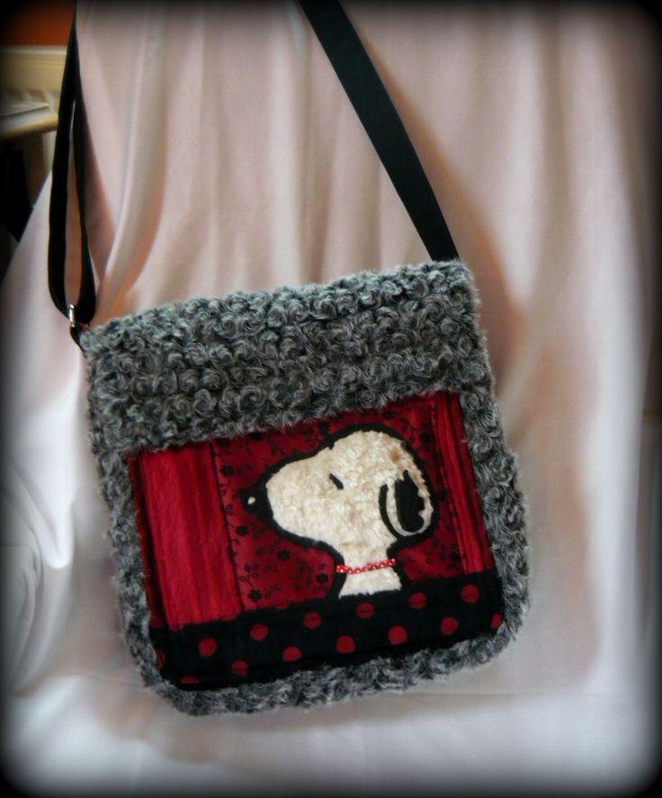 Snoopy táska -Handmade by Judy Majoros: a táska alapja szürke műszőrme, az elején a Snoopy pedig fehér műszőrméből és fekete filcből készült. Többféle pirosas árnyalatú textil került rá díszítésnek. az elején a piros rész az egy nagyobb zseb. A hátulján is van egy nagyobb, és két kisebb zseb, a két kicsi műbőrből készült. A belsejében kordbársony bútorszövet a bélés, és két zseb található benne. A zsebek a táskán mágneszárral, cipzárral és tépőzárral záródnak.
