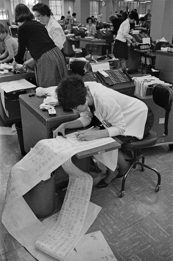 Pre-PC era; Bankers Trust, New York 1960. That huge sheet of paper the girl is pouring over is a computer print out. There were computers then. Just not the small PC's. Computers were immense machines occupying huge climate controlled rooms.