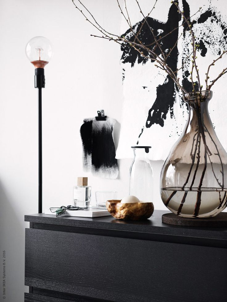 MALM byrå med 3 lådor i svartbrun, vilda vårkvistar i den vasen VÅRVIND i tonat glas, VARDAGEN karaff med lock, RODD golvlampfot, NITTIO LED ljuskälla E27 kopparfärgad.