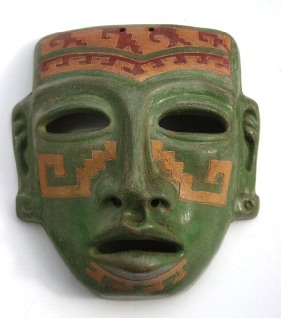 Interesting three dimensional anatomically correct tribal mask in earthy green with deep carved tribal marking on the cheeks chin and forehead.
