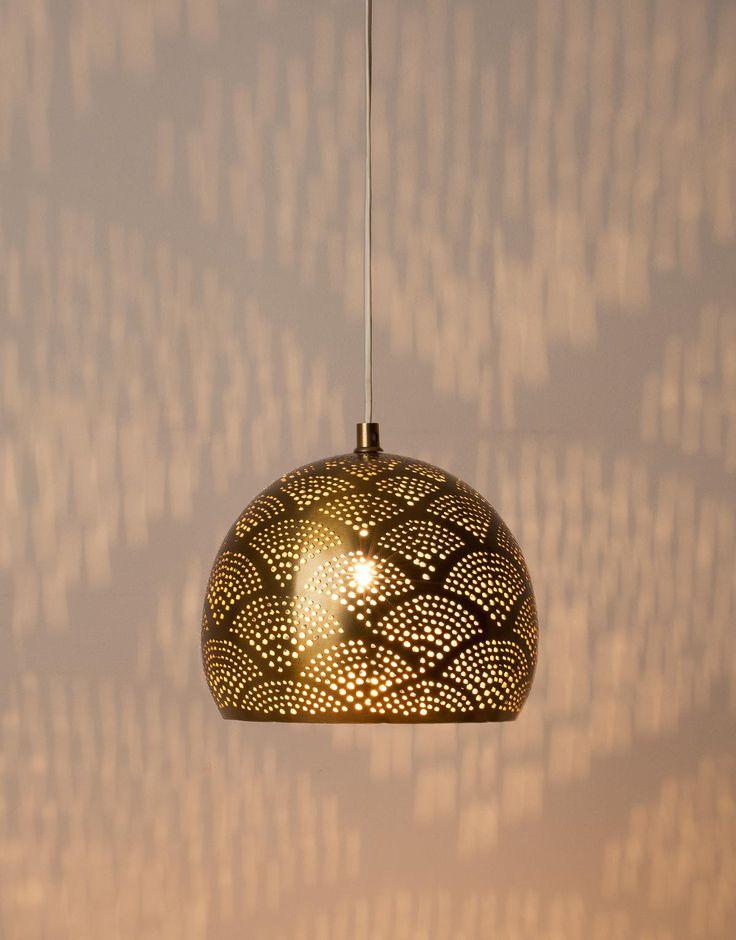 Vacker mässingsfärgad taklampa med hålmönster. Taklampan har vit sladd och mässingsfärgad takkopp mot tak. - Indiska