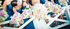 Complimented by her bridesmaids' unique bouquets, this bride carries a bouquet of white hydrangea, O'Hara garden roses, white callas, astilbe, ranunculas, white Majolica roses, and Ornithogalum arabicum. Floral design by Soirée Floral. Photo by Life Fusion Photography. See Less