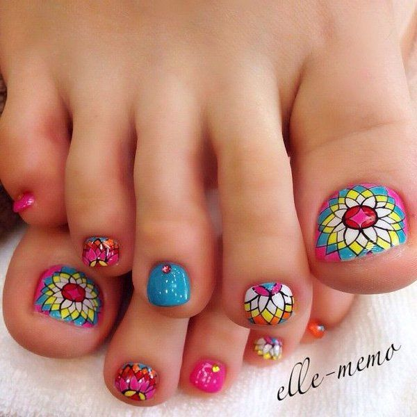 A mosaic flower inspired toenail art. Similar to those designs of chapel windows, this toenail art design uses bright and striking colors to create sharp images. The images are then overlapped into one another to form the flower design. Silver and pink beads are also added on top.