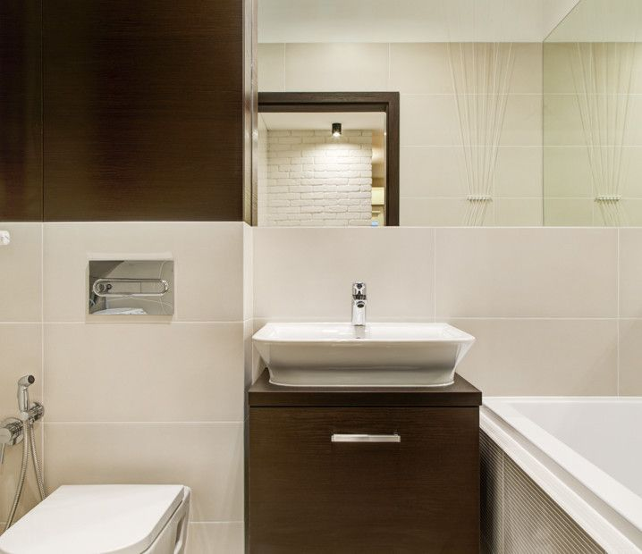 Aranżacja łazienki z drewnianymi elementami: szafka pod umywalkę oraz szafki ścienne.