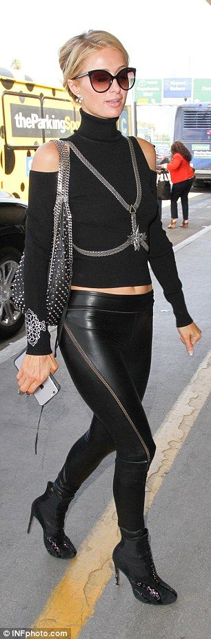 Flight fashion:The 35-year-old hotel heiress flaunted her lithe figure in a turtle neck which flashed her toned tummy along with a low slung pair of skintight leather pants with mesh-cut-outs