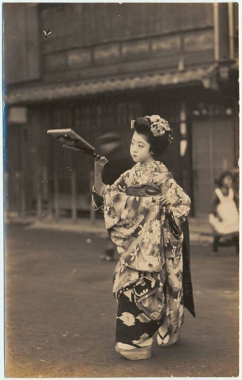 "Maiko (adolescent indentured to a geisha house since early childhood) ""playing"" battledore and shuttlecock for the camera. ca. 1900-1906"