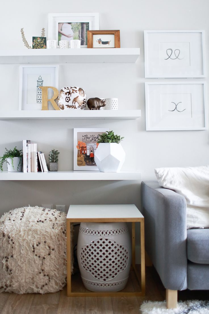 floor to ceiling wall shelving beside couch for toy and book storage tied…