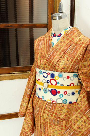サンセットブラウンやクリームイエロー、ハーブグリーンなどの色糸美しく、レトロタイルのような飾り格子が浮かび上がる正絹紬の単着物です。 #kimono