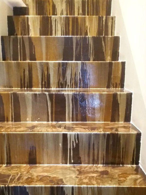Oro, nero e bianco per la scala rivestita in resina, con effetti diversi tra alzata e pedata.