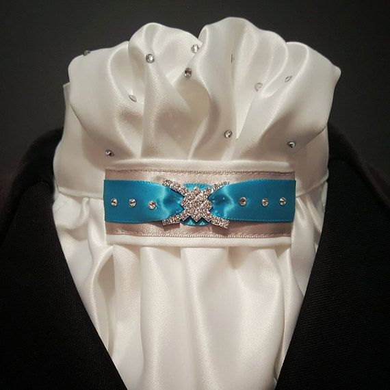 Stand out in the ring with a gorgeous stock tie with a pop of colour!  This stunning tie has a gathered centre with a silver and turquoise/tiffany blue tab.  The back has a velcro closure for easy on/off but we are happy to make with buttons if you wish.  Please check out our other beautiful design and our Facebook page has other accessories to complete your stylish look - www.facebook.com/eqpzazz  We welcome custom orders, please get in touch to discuss your requirements