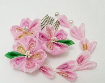 Kanzashi de primavera realmente bonita que es suave y encantador.  Este kanzashi consiste en flor principal 3.  Cada flor es de mano teñido de seda en tonos de púrpura pálido seafoam turquesa, pálida, pálida, y un azul púrpura con flores verdes las flores tienen estambres perlado plata. Las flores son de 3,5 pulgadas de ancho por 3 pulgadas de largo.  También hay 2 hebras de shidare que cuelgan. Son en los mismos colores y 5 pulgadas de largo y cada uno tiene una pequeña campana de plata en…