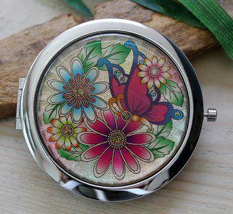 Metalen zakspiegeltje met vlinder en bloemen Mooi en handig zakspiegeltje. Met een druk op de knop opent zich het doosje, met daarin twee spiegeltjes. Eén ervan is een vergrotende spiegel. De voor-...