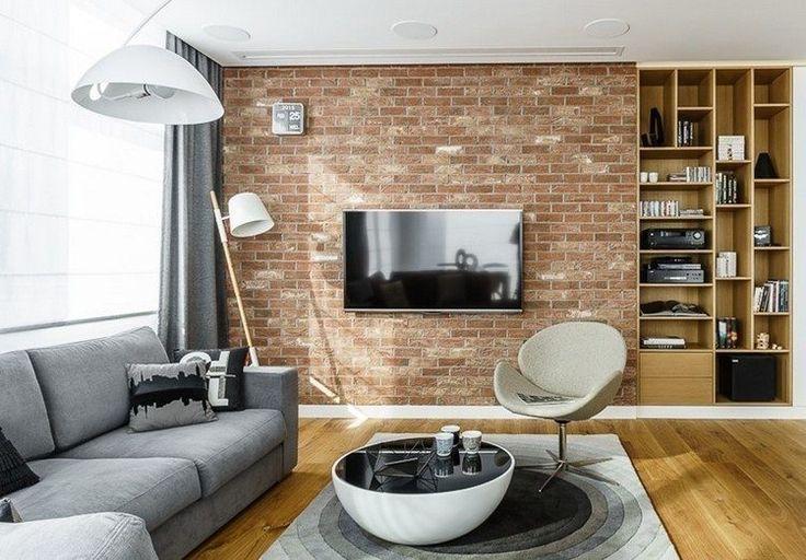 graues Sofa, runder Couchtisch und rote Ziegelwand