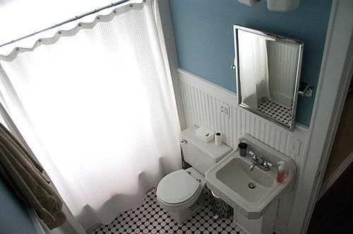 Wainscoting, chrome fixtures and mirror frame and black and white title give this bathroom a nice vintage look and feel.