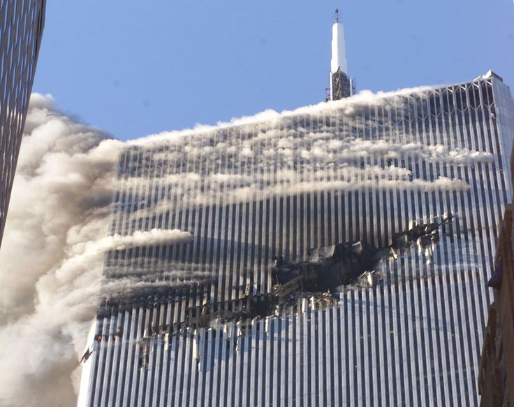 Smoke pours from a gaping hole and the upper floors of the World Trade Center's North Tower, shortly after hijackers crashed American Airlines Flight 11 into the building on September 11, 2001 in New York City. (AP Photo/Richard Drew)