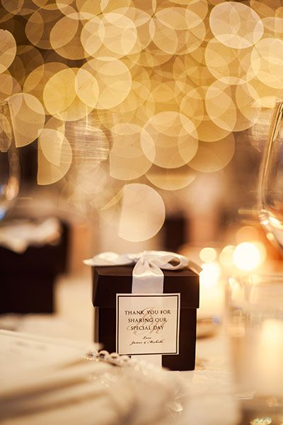 Elegant black boxes of macarons decorated each guest's place at the table. Image by Studio Impressions.