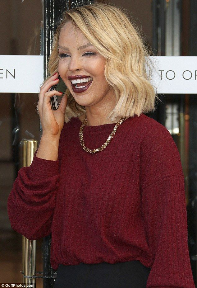 Bold beauty: She stuck to the fiery colour scheme with her red manicure which she flaunted while on a giggle telephone call