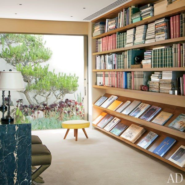 A vintage William Haines stool sits in the library, next to walnut bookshelves | archdigest.com