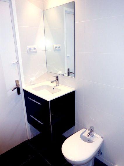 Reforma de baño y aseo. Combinación paredes en dos colores: blanco y negro, blanco y rojo, suelo porcelánico grafito, inodoros Roca, muebles Salgar, kit termostático ducha, plato Fiora, mampara Duritia.