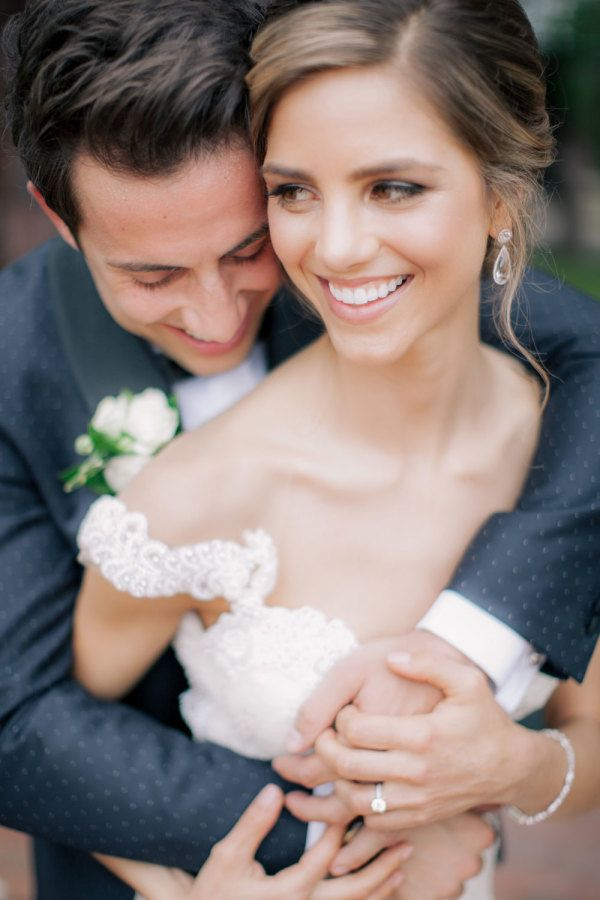 All smiles on this bride and groom's wedding day! http://www.stylemepretty.com/michigan-weddings/petoskey/2016/08/16/elegant-yacht-club-wedding-with-a-dreamy-designer-dress/ Photography: Clane Gessel - http://www.clanegessel.com/