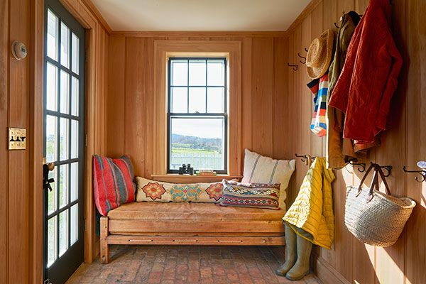 This snug mudroom has terrific views framed by blue-gray windows, edge-bead paneling, a sturdy brick floor, and a daybed nabbed at an antiques store in Millerton, New York.
