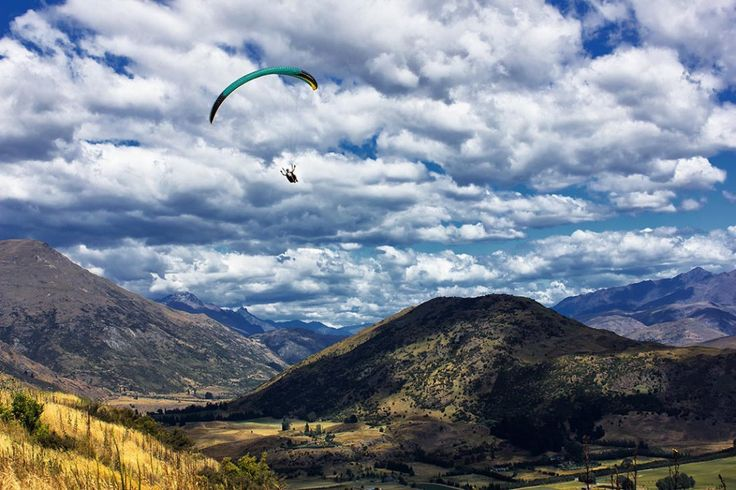 Paragliding through the mountains and rolling hills in the Crown Range - South Island, New Zealand ~