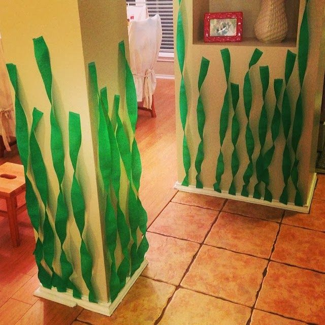 Twist green party streamers and tape to the wall to create a fun seaweed effect for a mermaid party! #MermaidBirthdayParty #MermaidParty #MermaidBirthday