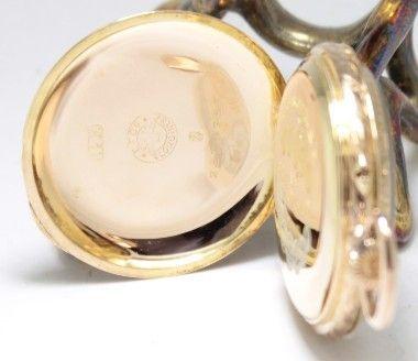 Trata-se de uma excelente peça em ouro 14k, que mede 3.4 cm de diâmetro, considerado relógio de peito.Possui uma bela caixa toda cinzelada manualmente, inclusive nos bordos, e teve sem dúvida pouco uso. Na tampa interior, também em ouro, as medalhas de prata ainda apresentam o banho original deste metal, garantia do seu excelente estado.  A sólida caixa toda em ouro 14k, devidamente contrastada e assinada, possui o número de série 2539753 , igual em ambas as tampas, datando a peça de 1911.