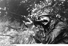 """A German Fallschirmjäger poses with his early model FG 42 (Ausführung """"C"""") in France, 1944."""